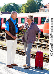 Mature aged couple at the station. Traveling on vacation -...