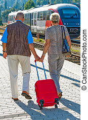 Mature aged couple at the station Traveling on vacation -...