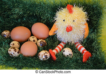 Easter scene with chick  and eggs in the spring meadow.
