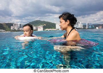 Asian Chinese mother and daugther playing at swimming pool -...