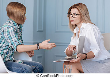 Pretty woman showing her laptop to a teenager - I do not...