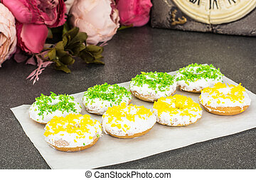 Small donuts with white frosting and colored sprinkles