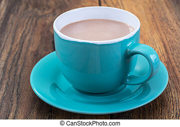 Coffee with milk in blue cup on wooden background