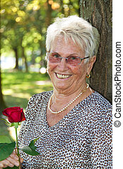 Older woman senior citizen with a red rose - Happy older...