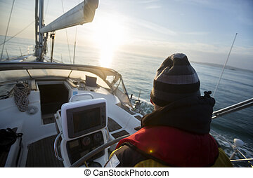 Rear View Of Man Steering Yacht At Helm - Rear view of...