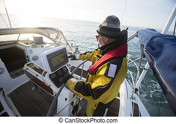 Man Operating Navigational Screen On Sail Boat In Sea -...