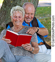 Mature couple in love seniors read a book.
