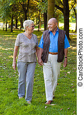 Mature couple in love is walking seniors - Mature couple in...