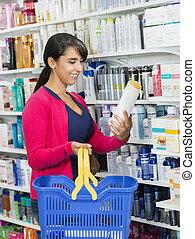 Customer Holding Shampoo Bottle In Pharmacy - Smiling female...