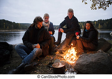 Friends With Coffee Cups Sitting Near Campfire - Multiethnic...