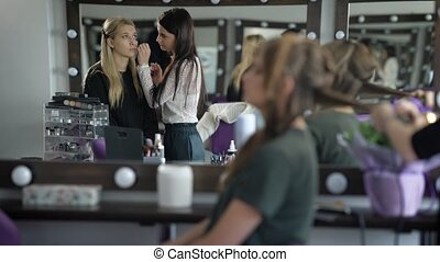 Two girlfriends in beauty shop. Girls prepare for a party. The makeup artist does a make-up to the fair-haired woman. Studio of beauty very cozy