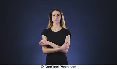 Serious young woman thinking about something on a dark background