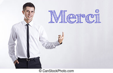 Merci - Young smiling businessman pointing on text -...