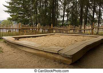 Sandpit at childrens playground, bounded by fence