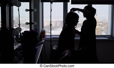 Hairdresser makes hairstyle for the model, but due to the fact that the whole picture is in the shade, we can not see their faces. Girls are in the dressing room in photo studio