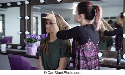 Female make-up artist and hairdresser of luxury beauty salon...