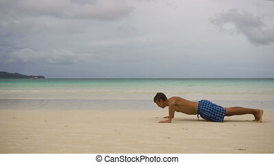 Man doing push-ups on the beach - Young man doing push ups...
