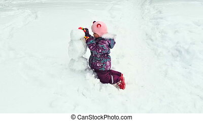 little girl molds snowman