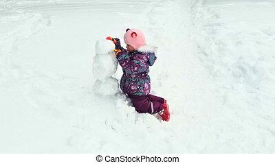little girl molds snowman