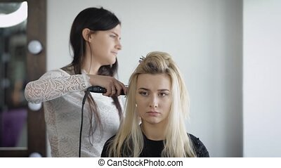 Scare new model sits on the hair at the hairdresser, which...