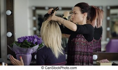 Female hairdresser of luxury beauty salon is working with...