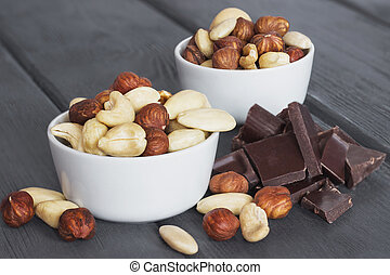 Set of nuts in bowl with chocolate on wooden background