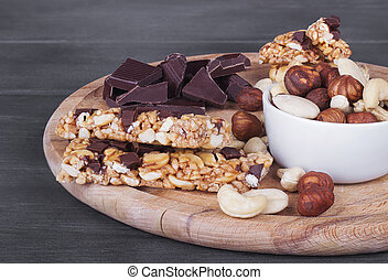 Granola bars, nuts, and  chocolate on wooden cutting board.