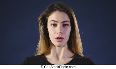 surprised young woman over dark background