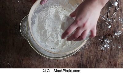 Top view of woman sieving flour in plate - Female hand pour...