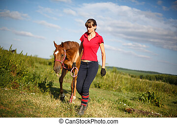 horsewoman jockey in uniform standing with horse