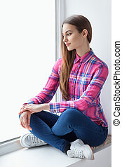 Young smiling woman sitting on window sill