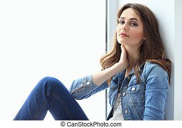 Portrait of beautiful woman relaxing on window sill -...