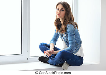 Young beautiful woman relaxing on window sill. Wellbeing...