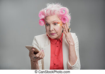 Senior woman with pink hair reading message - I am very...
