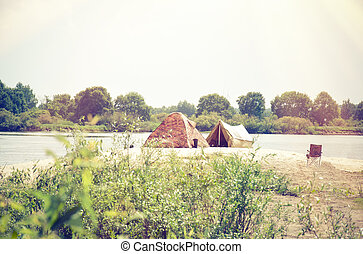 Camping tent near the river in the summer