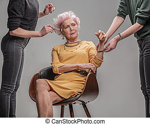 Serious elderly female sitting on chair in studio - Young at...