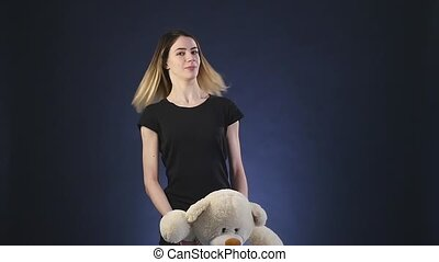 girl playing with teddy bear - Isolated on black slowmotion...