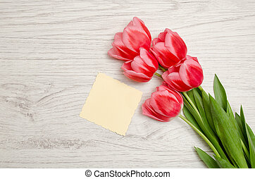 Small blank sheet of paper and pink tulips on a light wooden background. top view, space for text