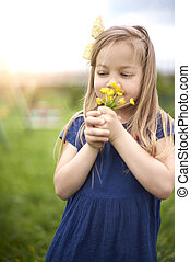 Little girl smelling bouquet of flowers