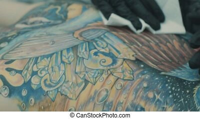 Master applying solution on the place for tattoo