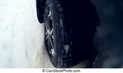 Snow flies into camera. Tire slipping and sliding on snow....