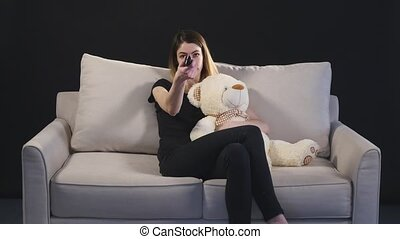 Young woman changing channels with remote control.