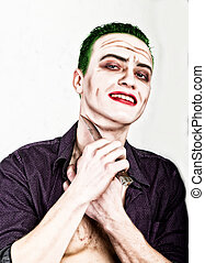 guy with crazy joker face holding knife, green hair and...