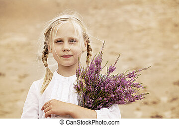 Cute Child Girl with Heather Flowers Outdoors