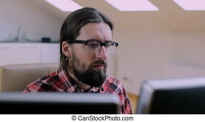 Bearded man in glasses working in office with 2 monitors