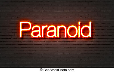 Paranoid neon sign on brick wall background.