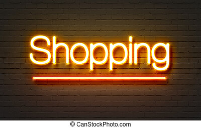 Shopping neon sign on brick wall background.