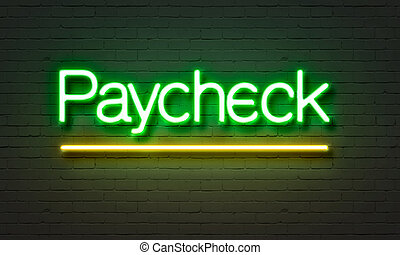 Paycheck neon sign on brick wall background.