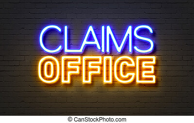 Claims office neon sign on brick wall background.