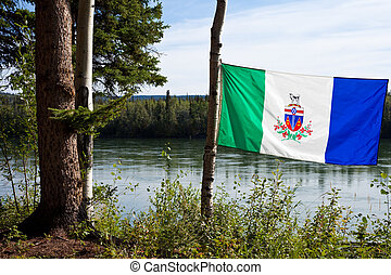 Yukon flag in front of Yukon River - Wind blowing Yukon...